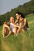 Smiling couple sitting in the grass