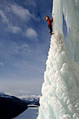Male ice climber ascending ice, Curtain Call, British Columbia, Canada