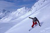 Snowboarding on mountain slope, Kuehtai, Tyrol, Austria