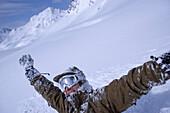 One man snowcovered, arms rising high, Kuehtai, Tyrol, Austria