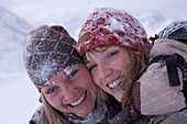 Two young women embracing together in snow, Kuehtai, Tyrol, Austria
