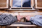 Two young women sunbathing, lying on bench of ski lodge, Kuehtai, Tyrol, Austria
