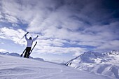 Young man with skis standing on snowcovered mountain, arms rising high, Kuehtai, Tyrol, Austria