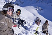 Young people having fun with snowball fight, sitting on snow, Kuehtai, Tyrol, Austria