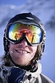 Young man wearing reflective ski googles, portait, Kuehtai, Tyrol, Austria
