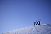 Four persons on snowcovered mountain, arms raising high, Kuehtai, Tyrol, Austria