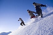 Group of young people running downhill snowcapped mountain, Kuehtai, Tyrol, Austria