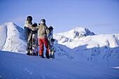 Young couple standing with snowboards, enjoying mountain view, Kuehtai, Tyrol, Austria