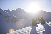 Young man and woman sitting on snow, clapping hands, Kuehtai, Tyrol, Austria