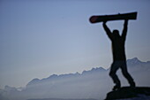 Person lifting up a snowboard, mountain chain in the background, Kuehtai, Tyrol, Austria