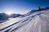 Two people on ski slope looking mountain panorama, Kuehtai, Tyrol, Austria