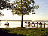 People sitting on jetty, St. Heinrich, Starnberger See, Oberbayern, Germany