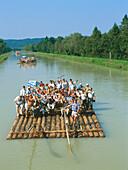 Group of people on wooden raft, River Isar, Pupplinger Au, Upper Bavaria, Germany