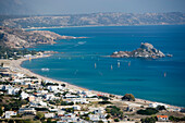 View over beach and bay of Kefalos with surfer to Kastri island with chapel St. Nicholas, Kefalos, Kos, Greece