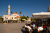 People sitting in a pavement cafe near Defterdar-Mosque at Platia Eleftherias, Kos-Town, Kos, Greece