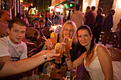 Young people toasting with drinks in an open-air bar at night , Kos-Town, Kos, Greece