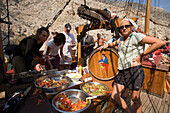 People using buffet on a sailing boat during a trip to a bay at Kalymnos, Greece