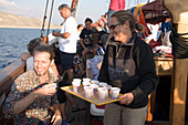 Woman serving drinks on board of a sailing boat during a trip to a bay at Kalymnos, Greece