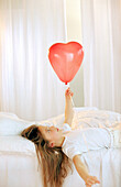 Girl holding red ballon
