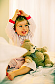 Toddler girl sitting with teddy sitting on bed, portrait