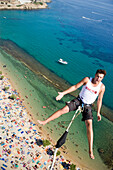 Young man bungee jumping over Paradise Beach, Mykonos, Greece