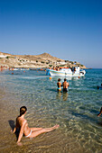 View over peopled Paradise Beach, Boat arriving, taking tourits to the beach,  Mykonos, Greece