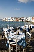 View along street with restaurants and bars, windmills in background, Little Venice, Mykonos-Town, Mykonos, Greece