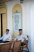 Two local men sitting in front of a tavern and having something to drink, Mykonos-Town, Mykonos, Greece