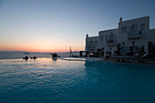 People lying in the fresh water pool and looking over the sea in the dusk, Apanema Resort Hotel, Mykonos-Town, Greece