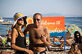 Man with sunglasses and a glass of water embracing woman with a crazy hat and sunglasses at Super Paradise Beach, knowing as a centrum of gays and nudism, Psarou, Mykonos, Greece