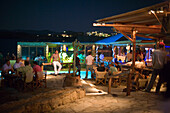 Tourists sitting in the open-air club of Cavo Paradiso, Paradise Beach, Mykonos, Greece