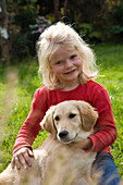 Blond 6 year-old girl holding Golden Retriever on meadow, Germany