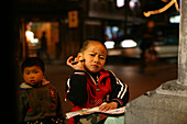 Shanghai,Old town, intersection, young boy doing homework under street lamp