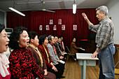 Singer and music conductor Peter Zhang,war Sänger in Revolutionsopern von Tschiang Tsching, Gattin von Mao, heute Rentner, dirigiert einen Hobby Chor, the former singer of revolutionary operas is now free to choose the songs he prefers, chorus of hobby si