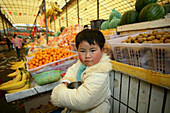 kid, child,young boy at the market stand of his parents, market hall, fruit and vegetables, Little Emperor