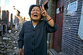 Abriss, demolitian Hongkou,Last residents of a demolished quarter, refusing resettlement, letzte Bewohner eines Abrissviertels, die sich der Umsiedlung widersetzen, redevelopment area, Abrissgebiet, living amongst demolished  houses, slum, old lady blames