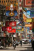 """Hongkou quarter Shanghai,Zhapu Lu, Straße, street, traditionelle Bebauung, Strassenkehrer, Reklame, Werbung, Werbetafeln, bicycle, Fahrrad, Strasse, street, Restaurant-Strasse, restaurants, brothels, shops, Bordell, Massagesalons, Leuchtreklame, aus: """"Myt"""