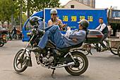 Traffic Shanghai,motorbike taxi, driver, courier, relaxed, lunch break, helmet, street junction