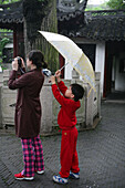 visitors taking photo in rain, umbrella, Yu Yuan Garden, Shanghai
