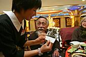 """Übersetzer Zhou Chun,translator Prof. Zhou Chun, shows a waitress a photo of him with Chou En Lai, war einst Dolmetscher von Tschou En Lai und Mao Tse Tung , Großer Vorsitzender, dann politisch verfolgt, """"Rechtsabweichler"""", Gefängnis, kommunstischer Terro"""