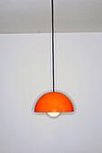 Orange 1970s style ceiling light in empty livingroom