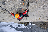 Climber climbing up vertical rock face, Cirque of the Unclimbables, Northwest-Territories, Canada