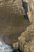 Man sitting on a rock high above virginia falls, Mackenzie Mountains, Northwest-Territories, Canada