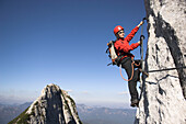 Young female climber on Donnerkogel fixed rope route, Dachstein Mountain, Austria