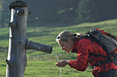 Young female hiker drinking water on a hiking trip, Salzburger Land, Austria