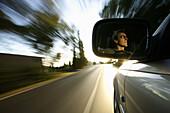 Man driving automobile, face in driving mirror, near Palafrugell, Costa Brava, Catalonia, Spain
