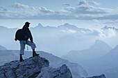 Hiker looking at mountains, Cristallo Group,  Dolomites ,Veneto, Italy