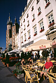 Tourists in cafe near the Church of Virgin Mary, Market Square in Cracow, Poland