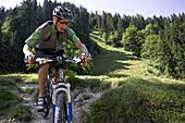 Mountainbiker downhill on path with broken stones, Bavaria, Germany