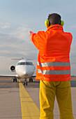 Airport ground crew signaling to aircraft, Airport Düsseldorf, North Rine-Westphalia, Germany